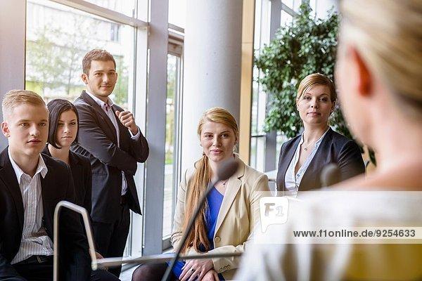 Geschäftsfrauen und -männer  die dem Redner im Konferenzraum zuhören.