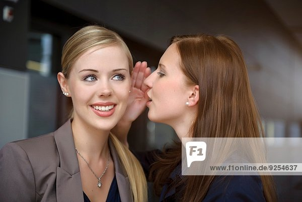Two young businesswomen whispering in office
