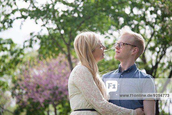 Junges Paar umarmt im Park