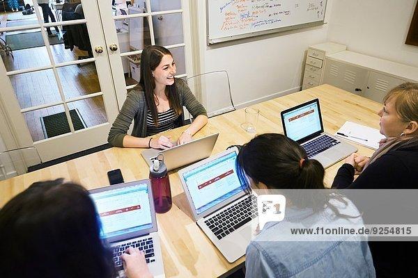 Weibliche Kollegen in einer Besprechung mit Laptops