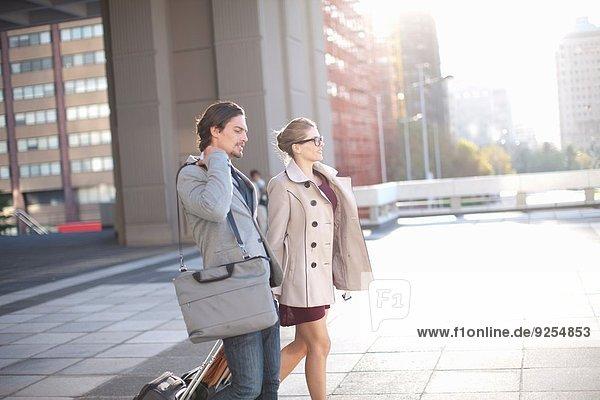 Geschäftsmann und Frau gehen über den städtischen Dachparkplatz