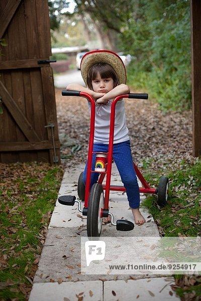Porträt eines vierjährigen Mädchens  das auf seinem Dreirad im Garten sitzt.