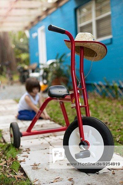 Dreirad vor dem vierjährigen Mädchen auf dem Gartenweg