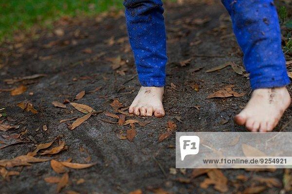 Schlammfuß eines vierjährigen Mädchens im Gartenboden stehend
