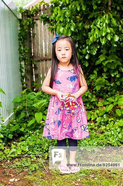 Portrait of serious young girl in garden with toy