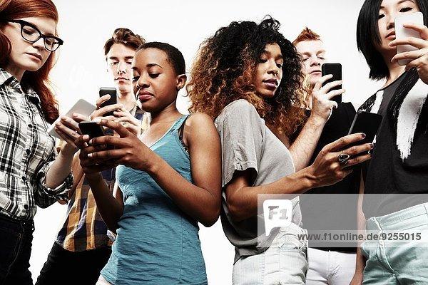 Niederwinkel-Studioaufnahme von sechs jungen Erwachsenen  die auf dem Smartphone texten.