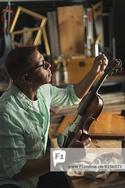Mature man fixing violin in his workshop
