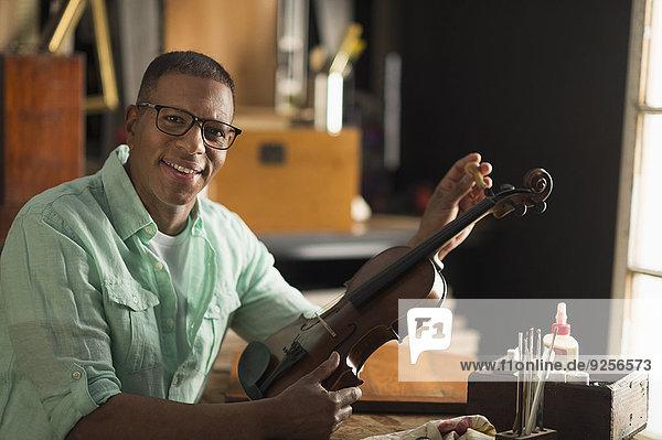 Portrait of mature man fixing violin in his workshop