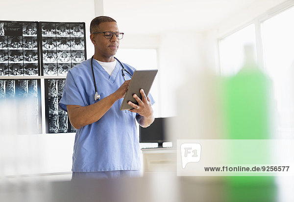 Male doctor in hospital using digital tablet