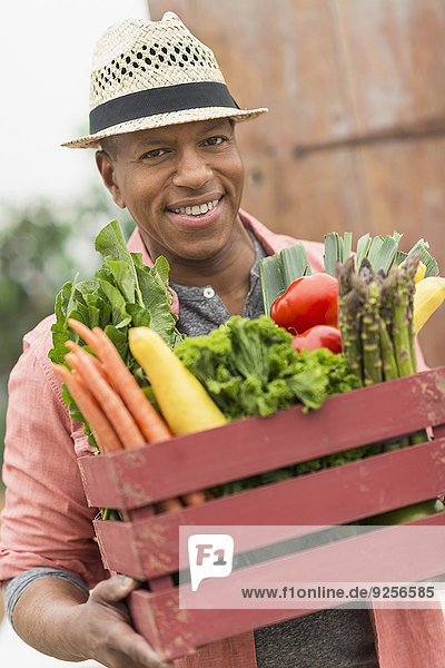 Portrait of man carrying crate full of fresh vegetables
