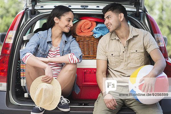 sitzend Auto offen Kofferraum jung