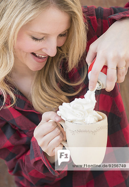 Portrait of woman spraying whipped cream into hot chocolate