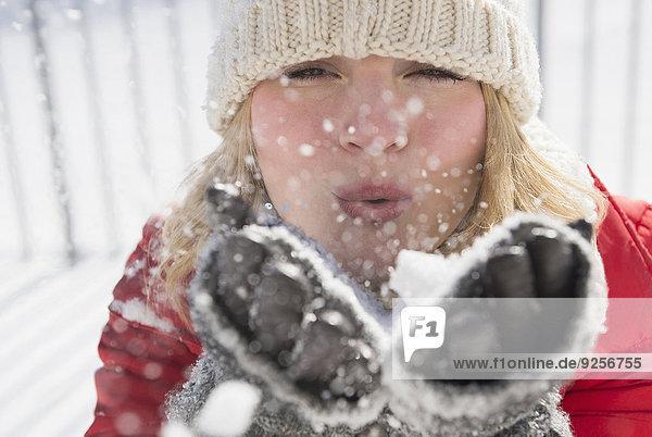 Portrait of woman wearing knit hat blowing snow