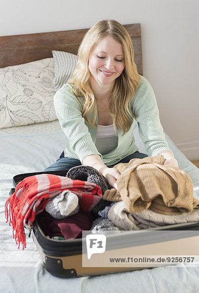 Woman sitting on bed and packing suitcase