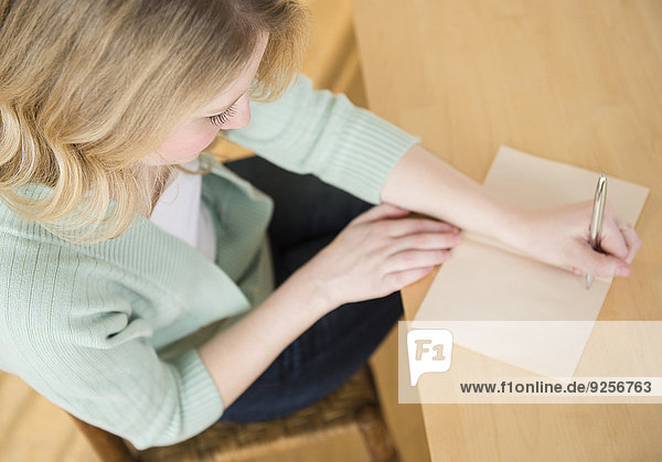 Blond woman sitting down and writting letter