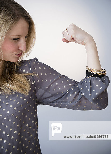 Portrait of blond woman showing muscle