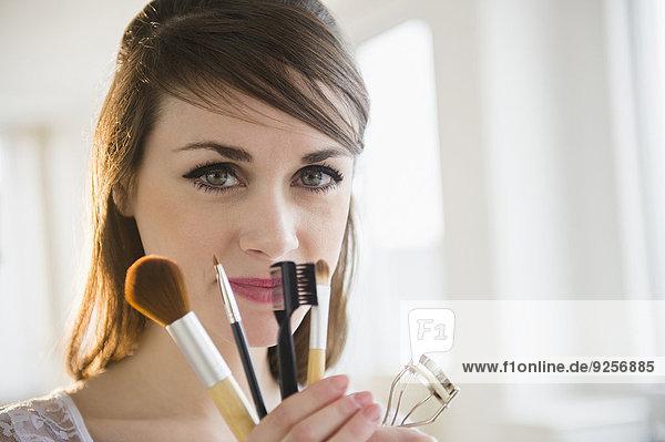 junge Frau junge Frauen Accessoire halten Schminke