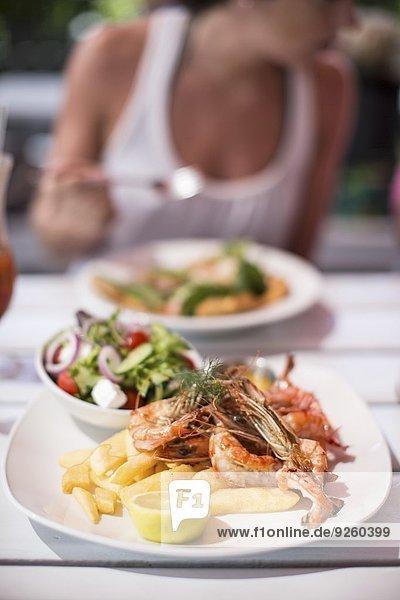 Garnelen mit Salat und Pommes im Gartenrestaurant