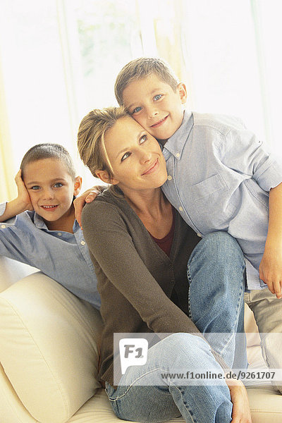 Mother and children smiling on sofa