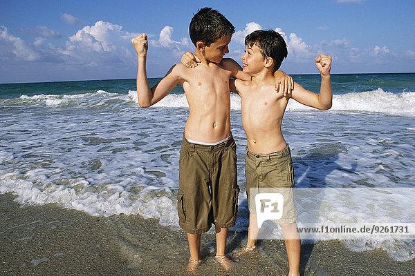 Boys flexing their muscles on beach