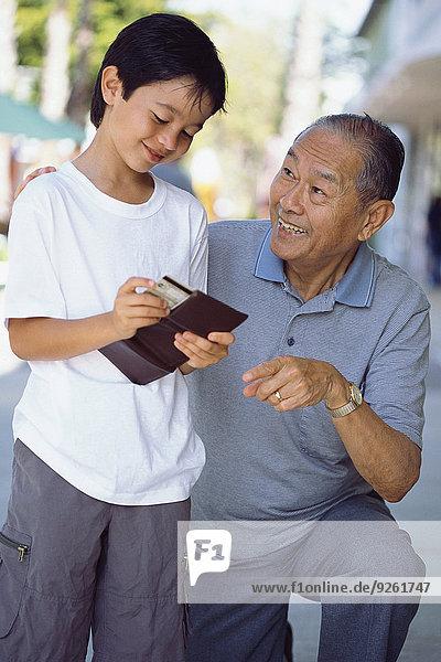 Senior Senioren Mann geben Enkelsohn Geld