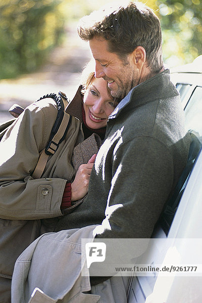 Couple hugging by car