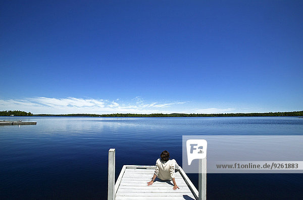 Woman overlooking lake on wooden dock