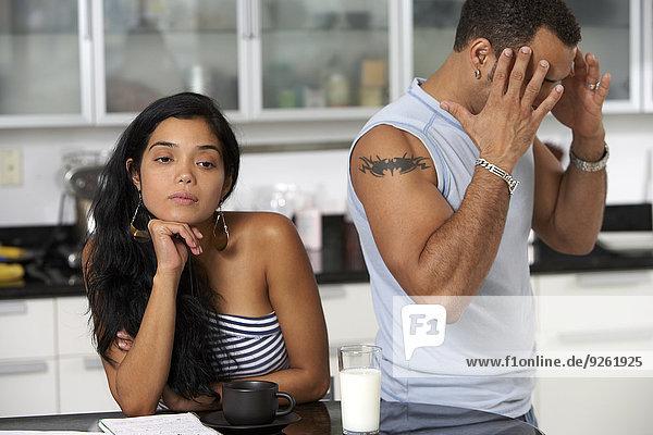 Hispanic couple arguing in kitchen