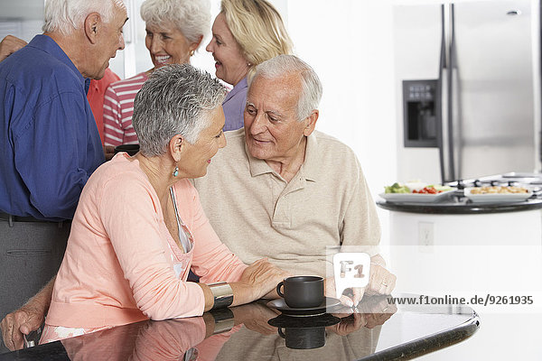 Senior couple having coffee in kitchen