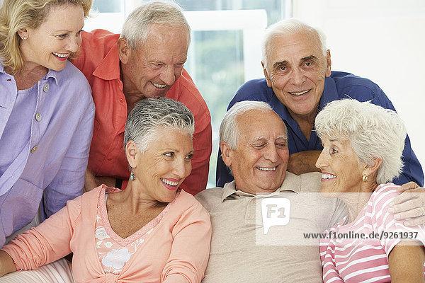 Senior friends talking in living room