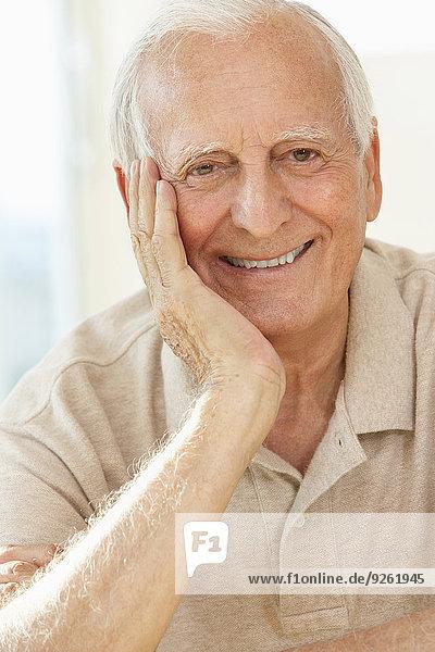 Senior man resting chin in hand