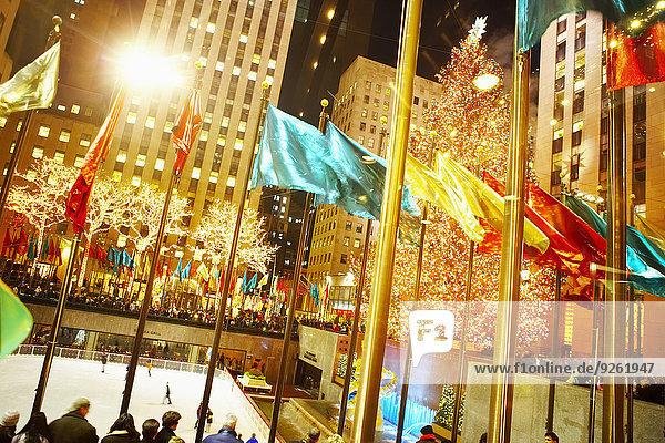 Flags flying over Rockefeller Center at night  New York  New York  United States