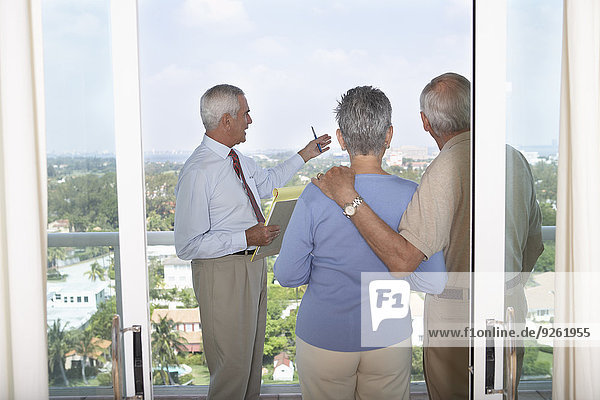 Realtor showing senior couple view from balcony