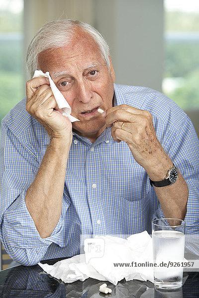 Senior man wiping his nose and taking medicine