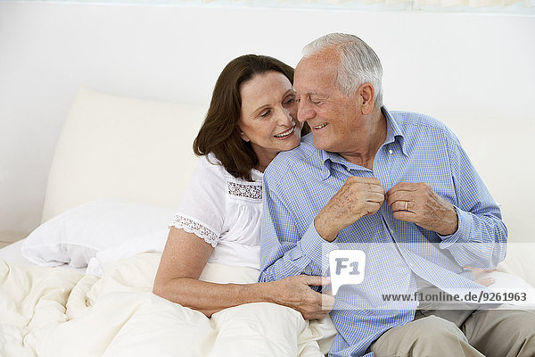 Senior couple hugging on bed