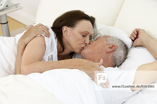 Senior couple kissing in bed