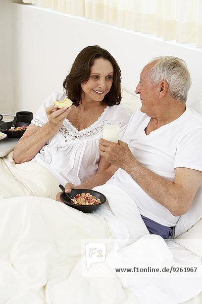 Senior couple eating breakfast in bed