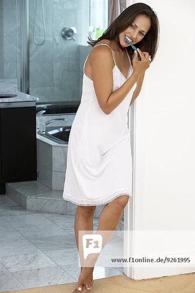 Indian woman brushing teeth in bathroom