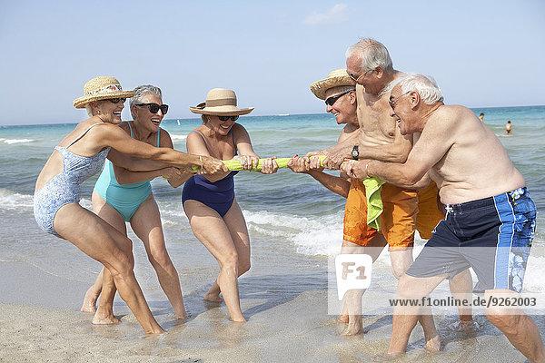 Senior Senioren Freundschaft Strand spielen Tauziehen