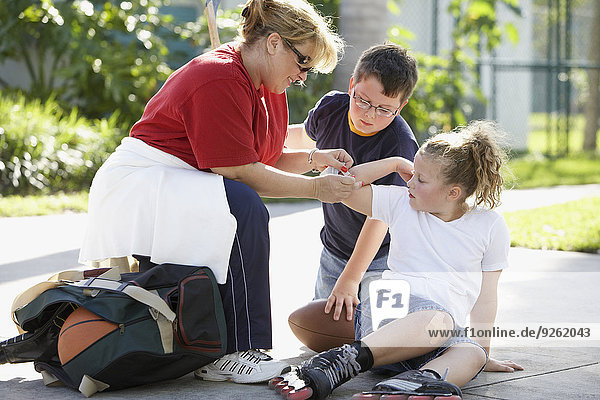 Mother bandaging daughter's scrape