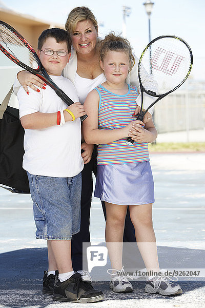 Mother and children holding tennis rackets outdoors