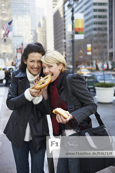 Women eating pretzel on city street