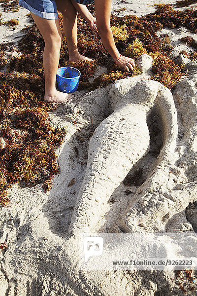 Mermaid sculpture in sand on beach