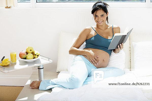 Frau Hispanier Bett Schwangerschaft vorlesen