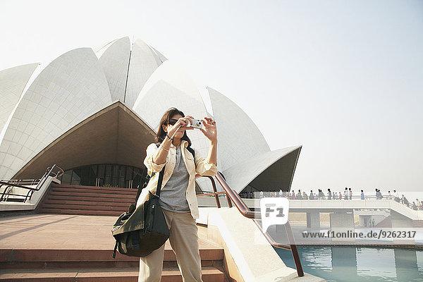 Caucasian tourist taking pictures at Bahai Temple  Delhi  India