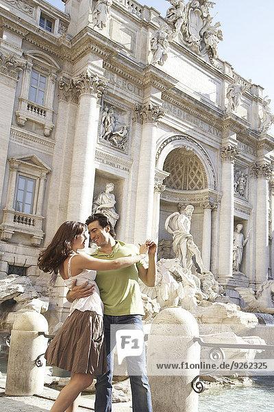 Caucasian couple dancing outside Fontana di Trevi  Rome  Italy