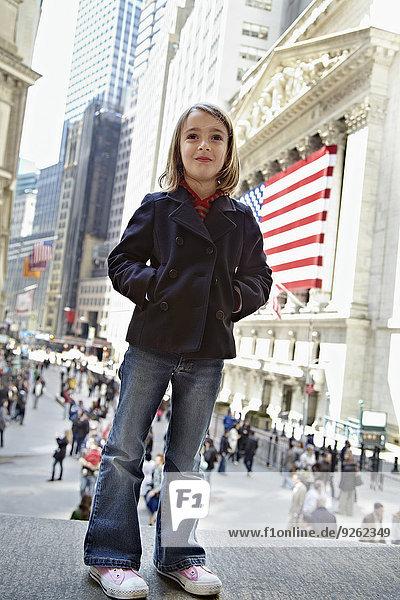 Girl standing outside New York Stock Exchange  New York City  New York  United States