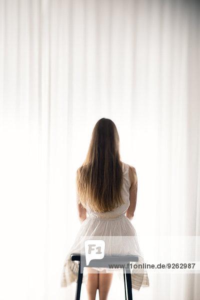 Junge Frau sitzt auf einem Hocker vor einem weißen Vorhang  Rückansicht