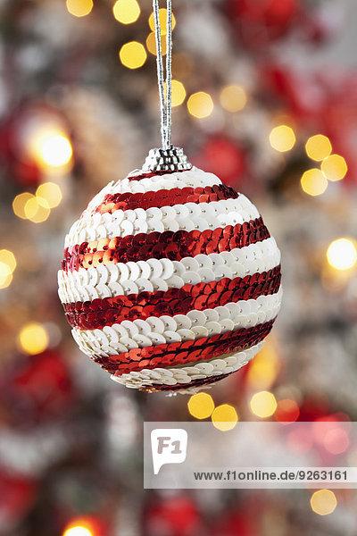 Weihnachtskugel geschmückt mit roten und weißen Pailletten vor verschwommenen Fackeln
