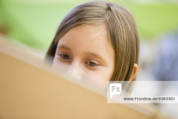 Schülerin beim Betrachten des Laptops  Teilansicht